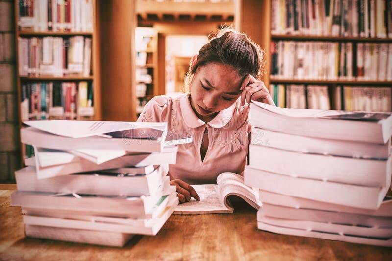 Gestraffte junge Frau, die in der Bibliothek studiert lizenzfreie stockfotografie