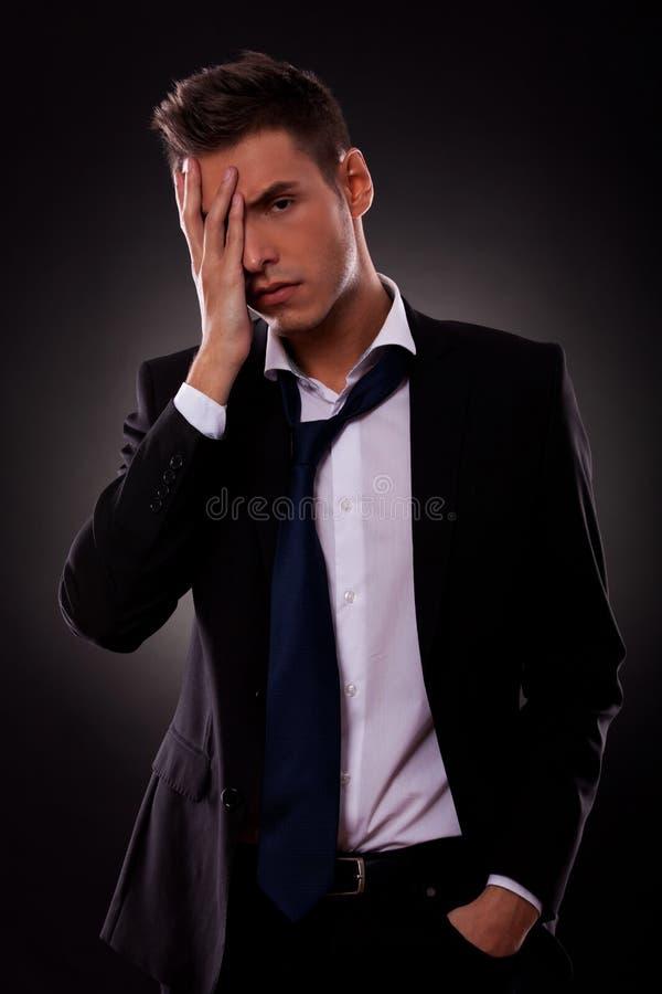 Gestraffter junger Geschäftsmann mit der Hand auf dem Gesicht stockfotos