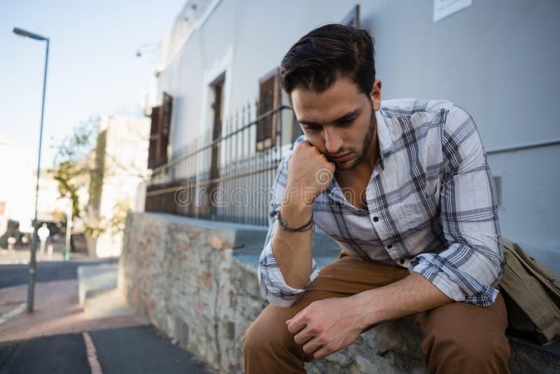 Gestraffter Mann, der unten beim Sitzen auf Stützmauer schaut stockfotografie