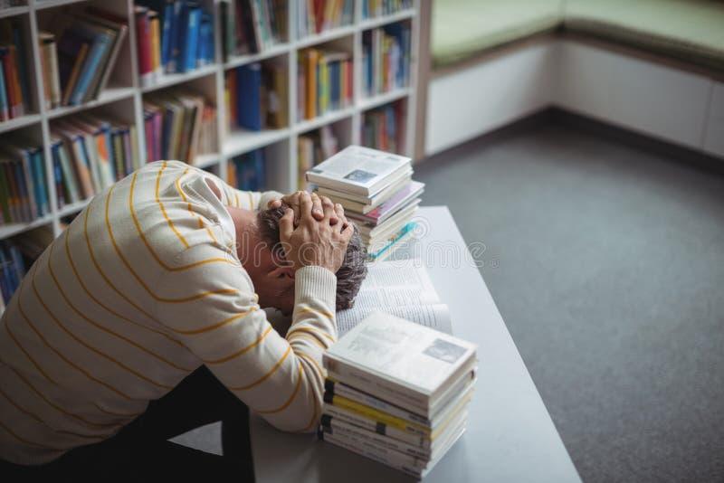 Gestraffter Schullehrer, der auf Tabelle in der Bibliothek sich lehnt stockbilder