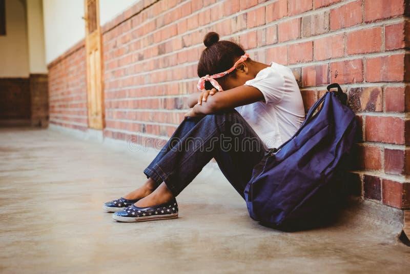 Gestrafftes Mädchen, das gegen Backsteinmauer im Schulkorridor sitzt lizenzfreies stockbild