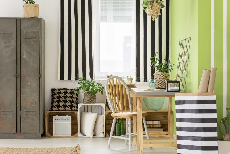 Gestreept bed naast houten stoel bij bureau in groene werkruimte inte stock afbeelding