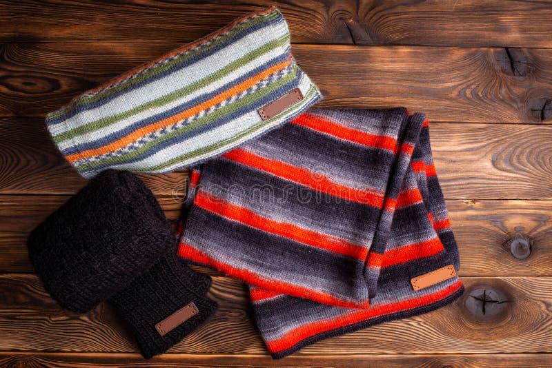 Gestreept brei gestreepte sjaals en zwarte gebreide kokers op houten achtergrond stock fotografie