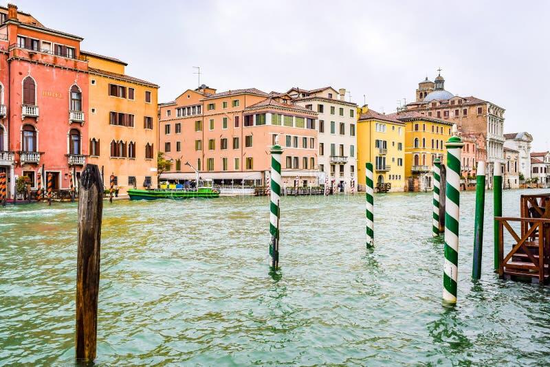 Gestreepte en houten meertrospolen langs kanten van Grand Canal in Venetië, Italië stock foto
