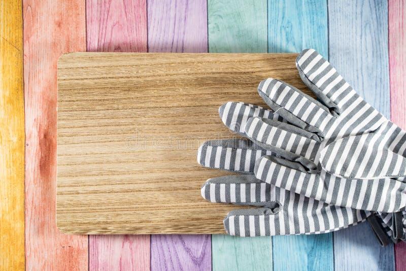 Gestreepte het tuinieren handschoenen op een houten plank, over een achtergrond van de pastelkleur houten regenboog Nuttig voor d royalty-vrije stock foto's