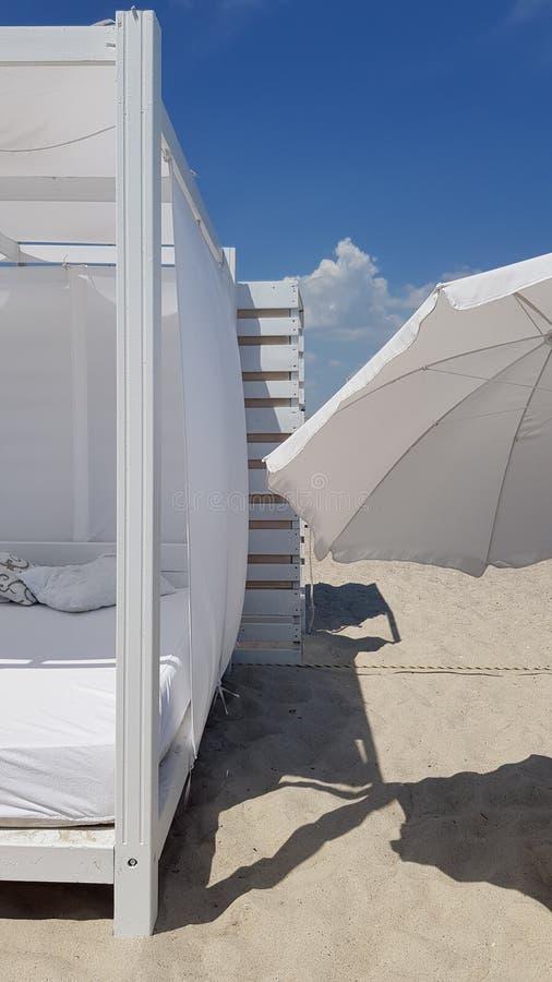Gestreepte houten muur met wit zonnescherm en witte textielparasol royalty-vrije stock foto