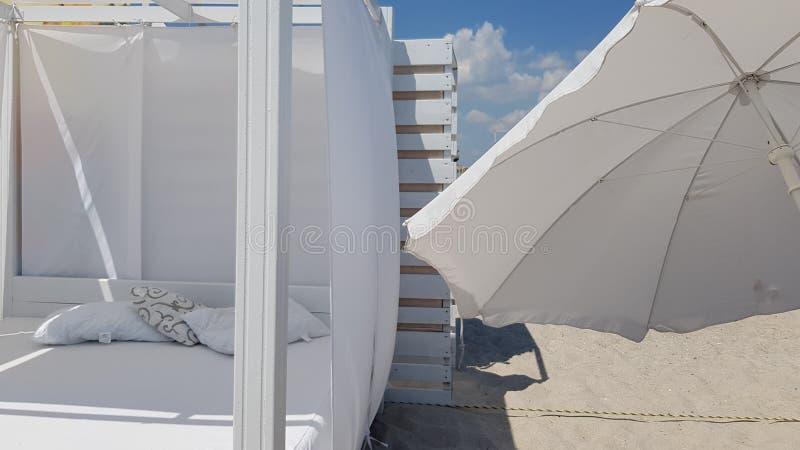 Gestreepte houten muur met wit zonnescherm en witte textielparasol stock foto