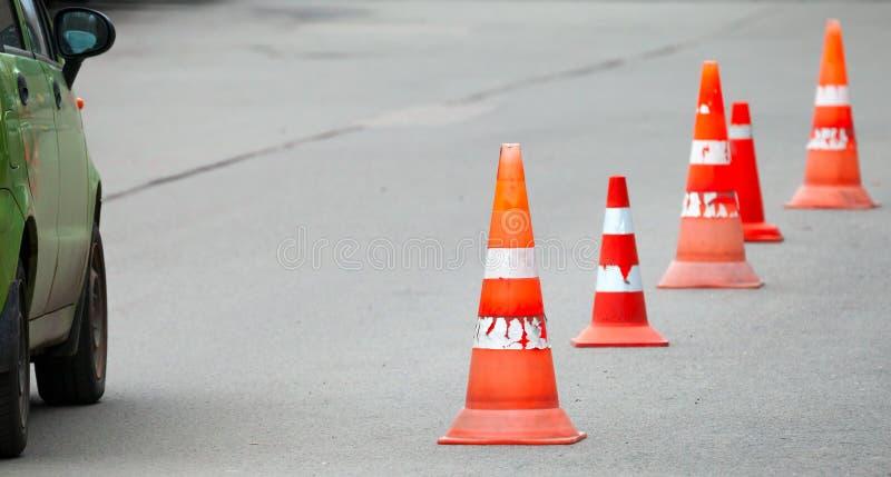 Gestreepte oranje kegels op de weg stock afbeeldingen