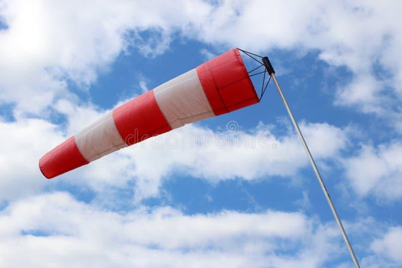 Gestreepte windsock bij luchthaven op de achtergrond van mooie wolken stock afbeelding