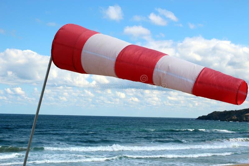 Gestreepte windsock, naast de oceaan stock fotografie