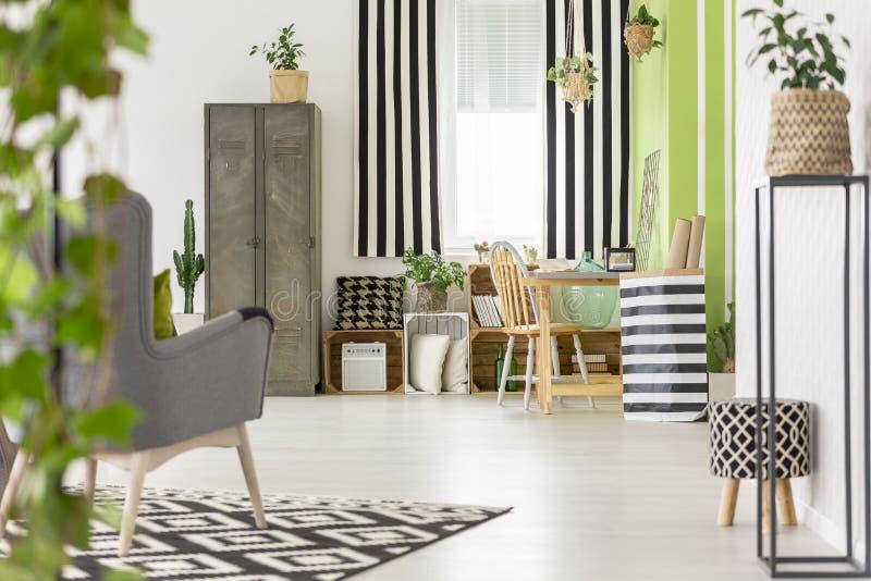 Gestreift drapiert im modernen Wohnungsinnenraum mit Metallkabinett a stockfotos