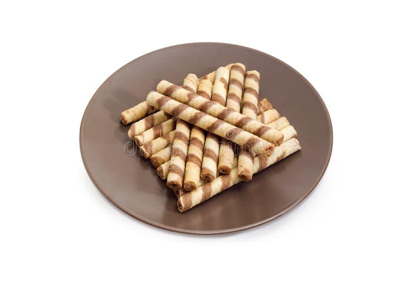 Gestreifte Oblatenröhrchen mit der Schokolade, die auf braunen Teller füllt stockfotos