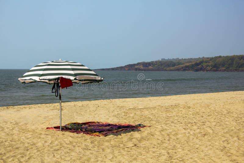 Gestreifter großer Regenschirm und Saronge auf dem mit gelbem Sand des Strandes gegen den Ozean mit Meereswellen unter einem klar stockfoto