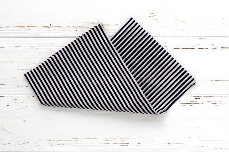 Gestreifter Küchenstoff auf weißem Weinleseholztisch Kopieren Sie Platz stockfoto