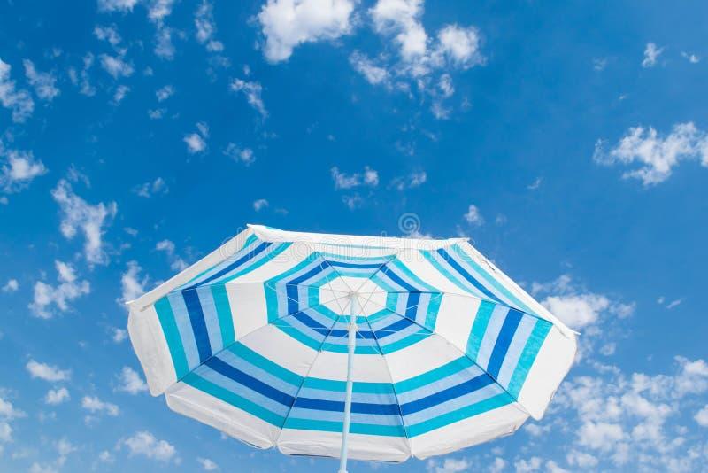 Gestreifter Strandschirm unter blauem Himmel lizenzfreies stockbild