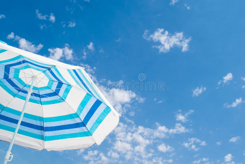 Gestreifter Strandschirm unter blauem Himmel stockfotografie