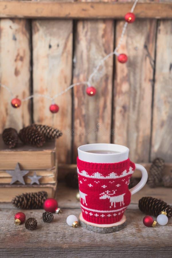 Gestrickte rote Schale mit weißem Ren, Weihnachtslichtern mit alten Büchern, Kegeln und Spielwaren am Hintergrund stockfoto