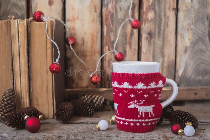 Gestrickte rote Schale mit weißem Ren, Weihnachtslichtern mit alten Büchern, Kegeln und Spielwaren am Hintergrund lizenzfreie stockbilder