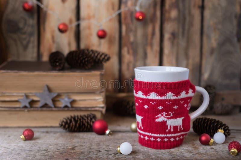 Gestrickte rote Schale mit weißem Ren, Weihnachtslichtern mit alten Büchern, Kegeln und Spielwaren am Hintergrund lizenzfreie stockfotografie