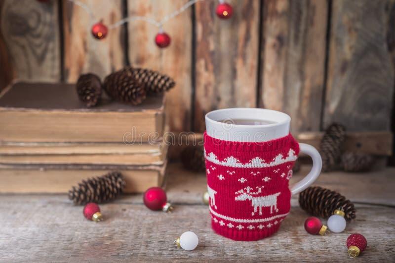 Gestrickte rote Schale mit weißem Ren, Weihnachtslichtern mit alten Büchern, Kegeln und Spielwaren am Hintergrund stockbild