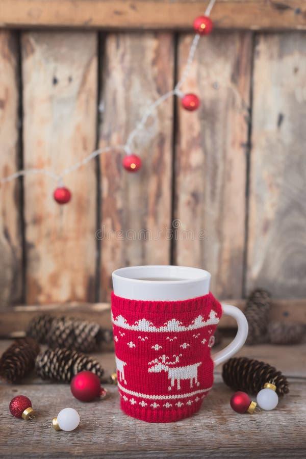 Gestrickte rote Schale mit weißem Ren, Weihnachtslichtern mit Kegeln und Spielwaren am rustikalen Hintergrund stockfotos