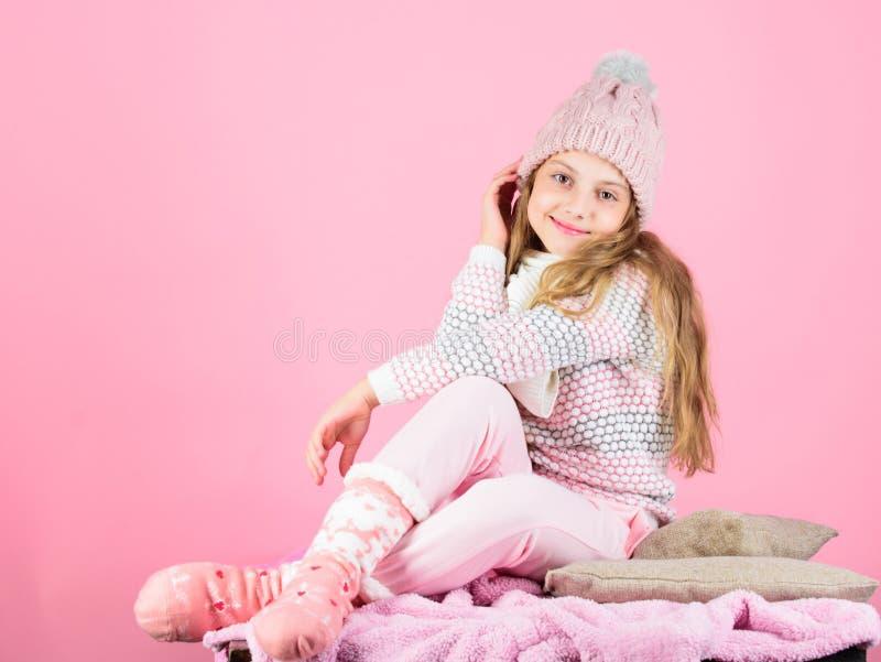 Gestrickter warmer Hut des Kindermädchens Abnutzung, der rosa Hintergrund sich entspannt Warmes Kleidungskonzept der Wintermode K stockfotos