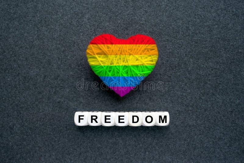 Gestricktes Herz mit homosexueller Regenbogenflagge Lgbt und Wörter Freiheit auf a stockfoto