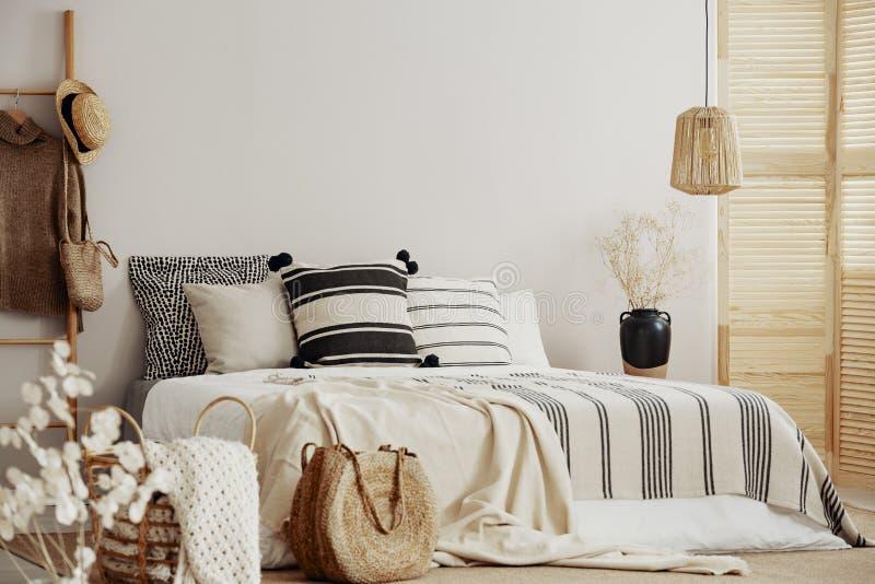 Gestript beddegoed op het witte bed van de koningsgrootte, exemplaarruimte op lege muur stock afbeeldingen