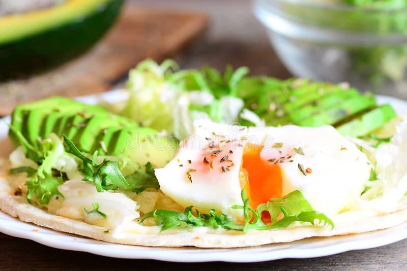 Gestroopt ei, avocadoplakken, salademengeling, Chinese kool, droge kruiden, saus op een tortilla Heerlijke tortilla met het vulle royalty-vrije stock foto's