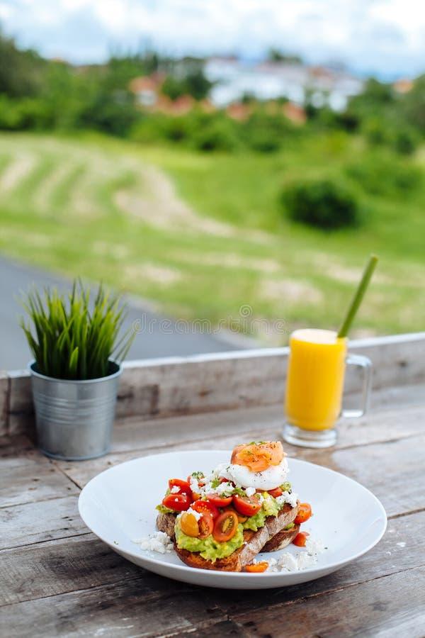 Gestroopt Ei op toost met tomaten, avokado, kaas en zalm en Sinaasappel smoothie op geweven achtergrond Gezond Ontbijt Verti royalty-vrije stock fotografie