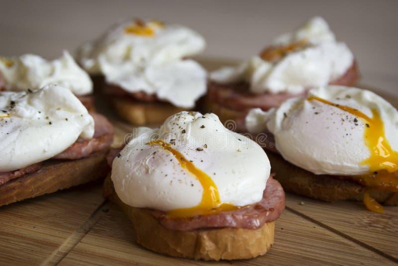 Gestroopte eieren met brood en ham voor Ontbijt stock foto