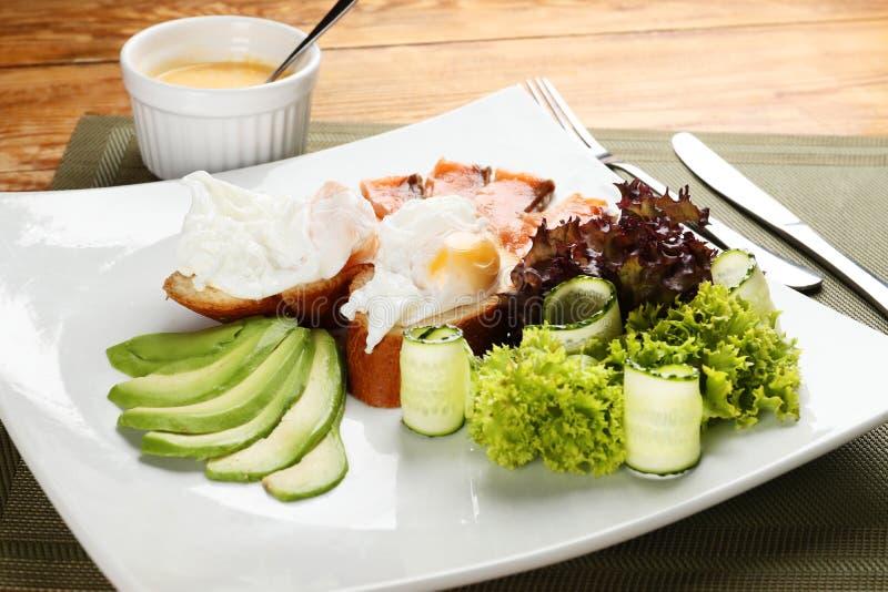 Gestroopte eieren op toost met zalm en avocado royalty-vrije stock foto