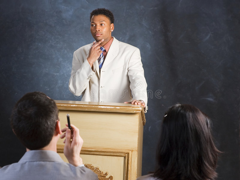 Gesture. A man speaking from a podium, with a look of contemplation royalty free stock images