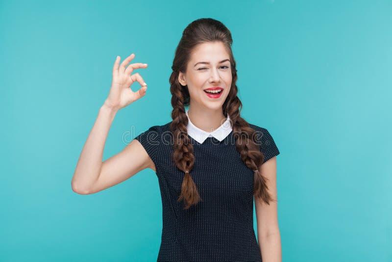 Gesture il sorriso a trentadue denti della donna e la mostra del segno giusto alla macchina fotografica fotografia stock