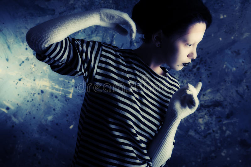 Gesture of a mime. Portrait of a female mime in sailor's striped vest royalty free stock photography