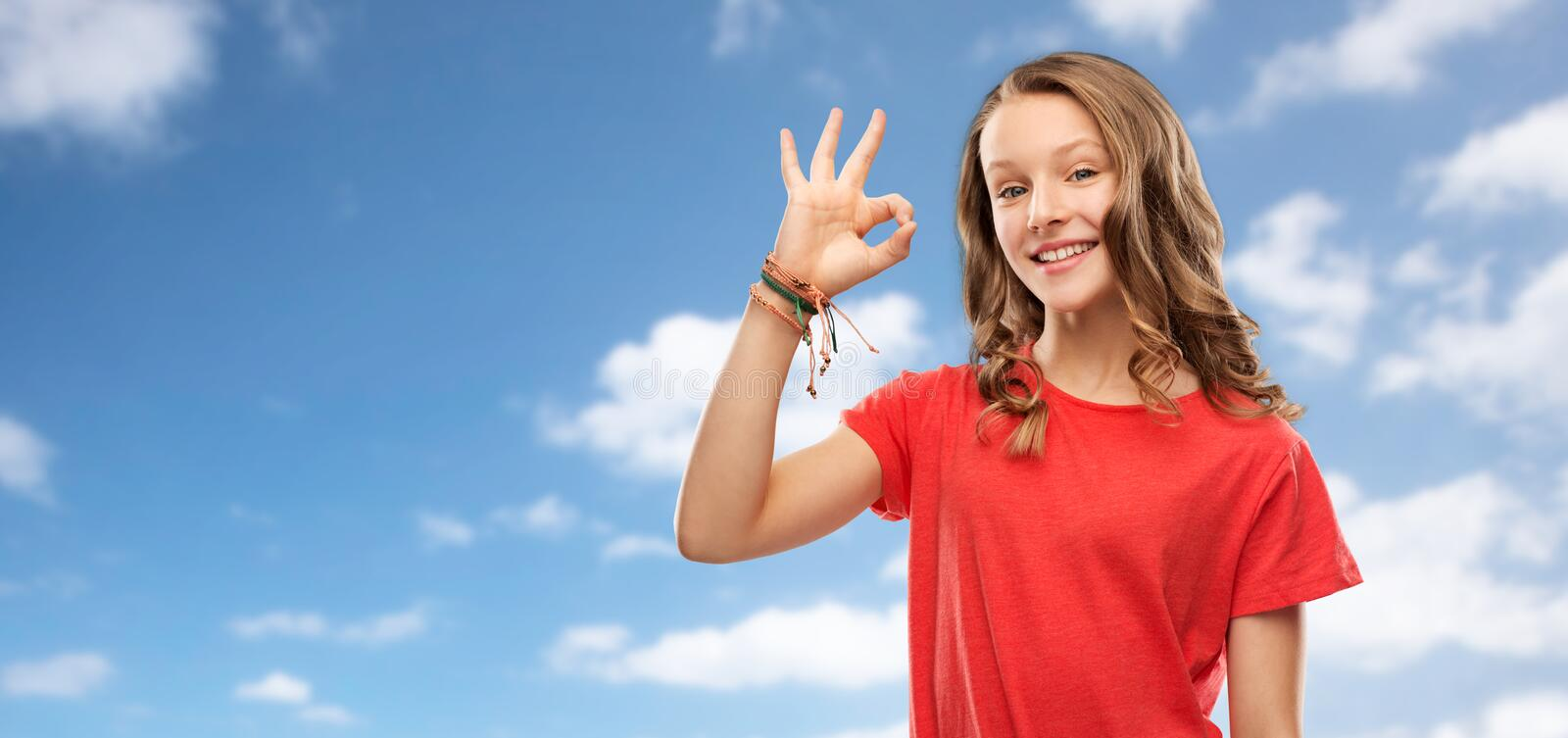 Smiling teenage girl in red t-shirt showing ok royalty free stock images