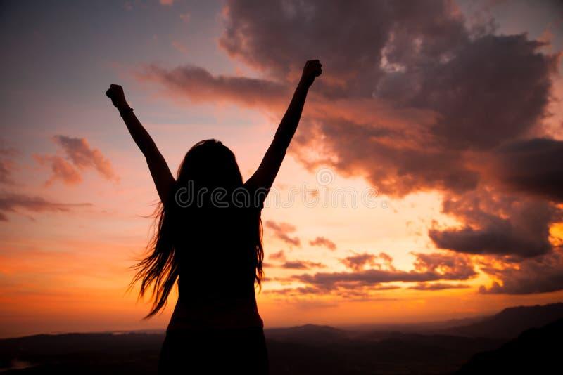 Gesturing επιτυχία γυναικών - σκιαγραφία πέρα από τον ουρανό βραδιού στοκ φωτογραφίες με δικαίωμα ελεύθερης χρήσης