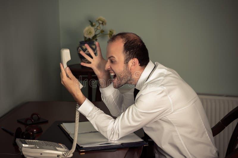 Gesturing dell'uomo di affari aggressivo e grido sul telefono fotografie stock