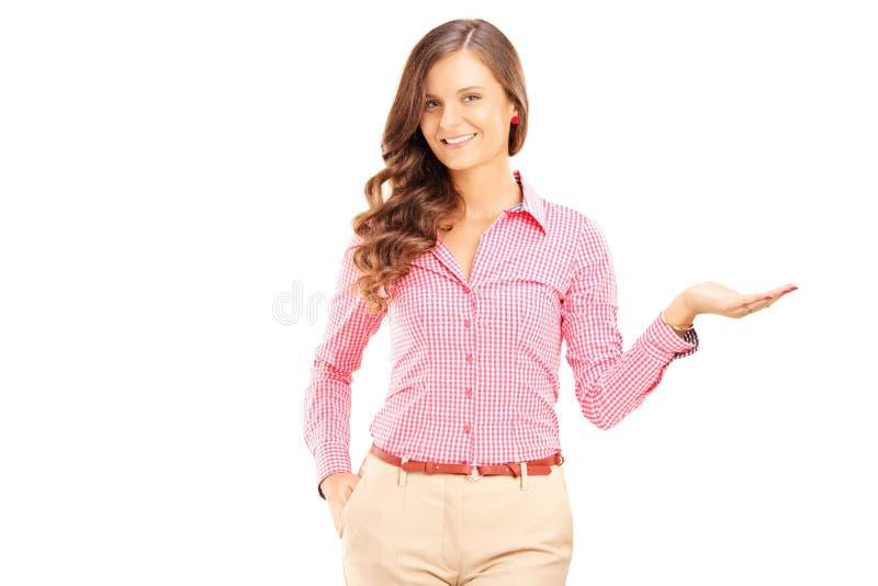 Gesturing Femminile Sorridente Con La Sua Mano Ed Esaminare Macchina Fotografica Immagine Stock Libera da Diritti