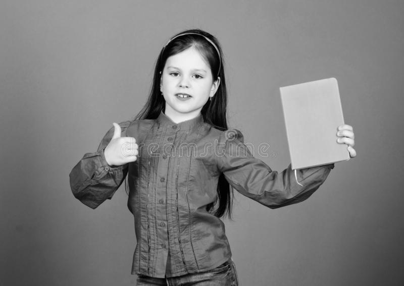 Gesturing thumbs up to reading. Adorable small child approving book for home reading. Cute little girl giving approval stock photo