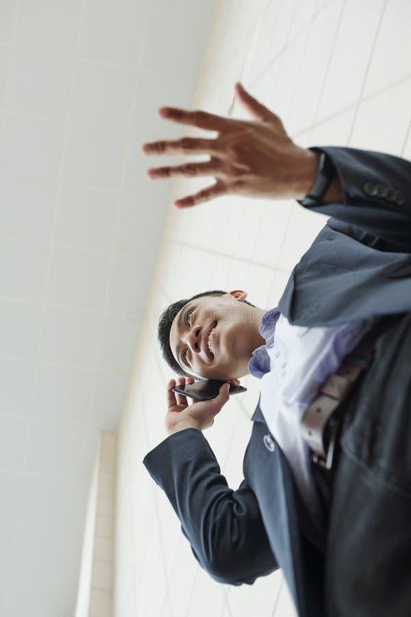 Gesturing uomo d'affari che rivolge al telefono immagini stock