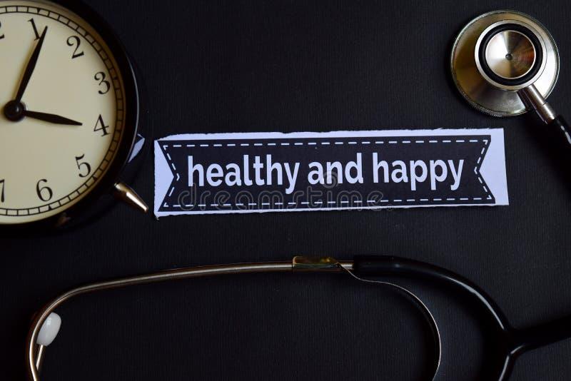 Gesund und glücklich auf dem Druckpapier mit Gesundheitswesen-Konzept-Inspiration Wecker, schwarzes Stethoskop stockfotos