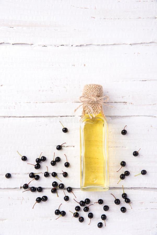 Gesund und reich im Vitaminöl der Beerenvogelkirsche auf einem woode lizenzfreie stockfotos