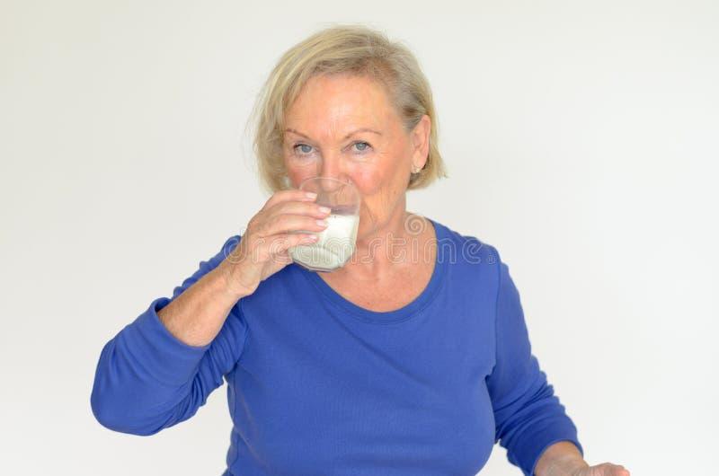 Gesunde ältere Dame, die frische Milch trinkt stockfotografie