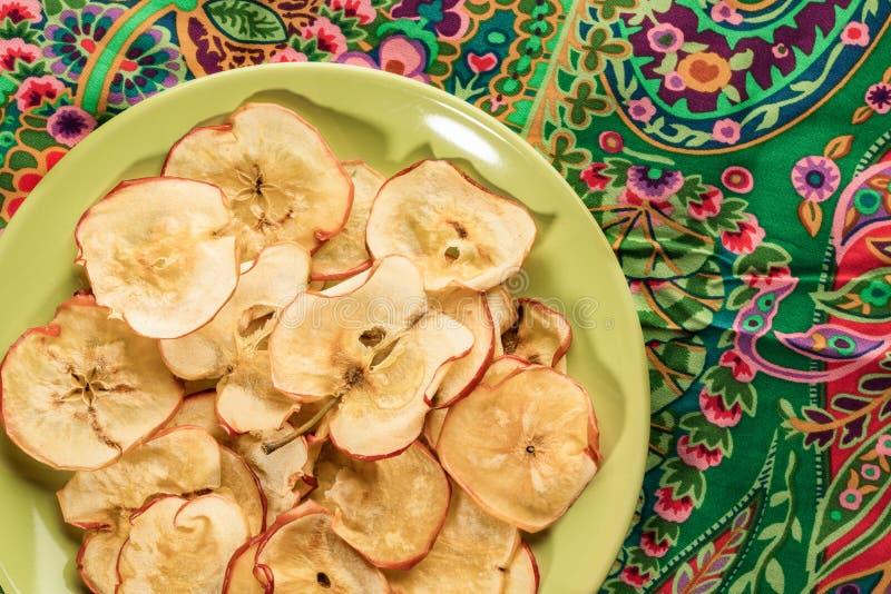 Gesunde Apfelchips der Nahaufnahme auf runder gr?ner Platte auf gr?nem Blumengewebe stockfotografie