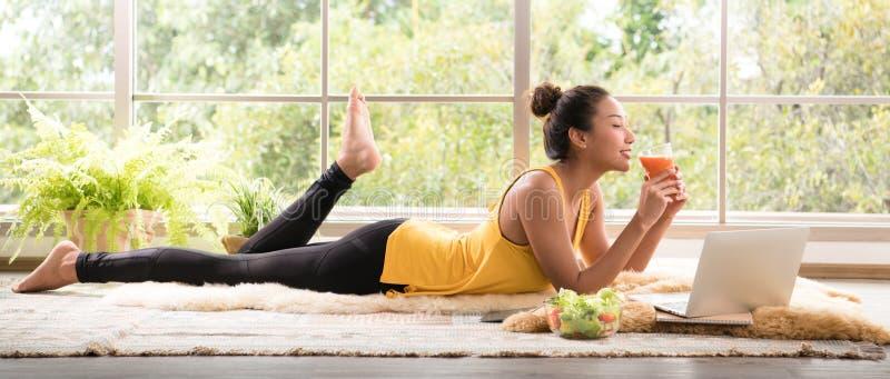 Gesunde Asiatin, die auf dem Boden isst den Salat schaut entspannt und bequem liegt stockbilder