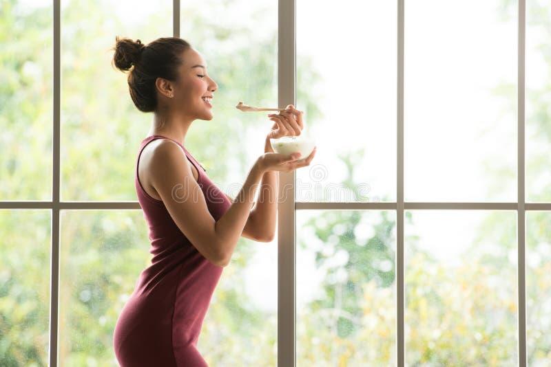 Gesunde Asiatinstellung und Halten einer Schüssel Joghurts schauend entspannt und bequem lizenzfreie stockbilder