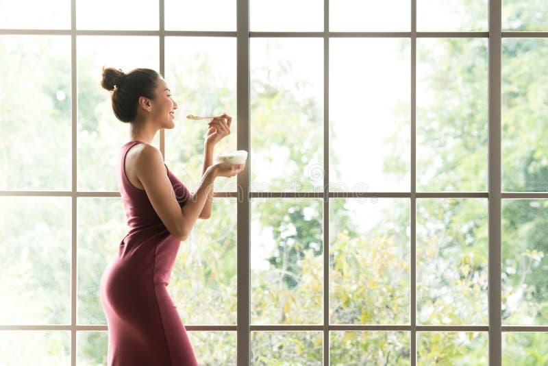 Gesunde Asiatinstellung und Halten einer Schüssel Joghurts schauend entspannt und bequem stockbild