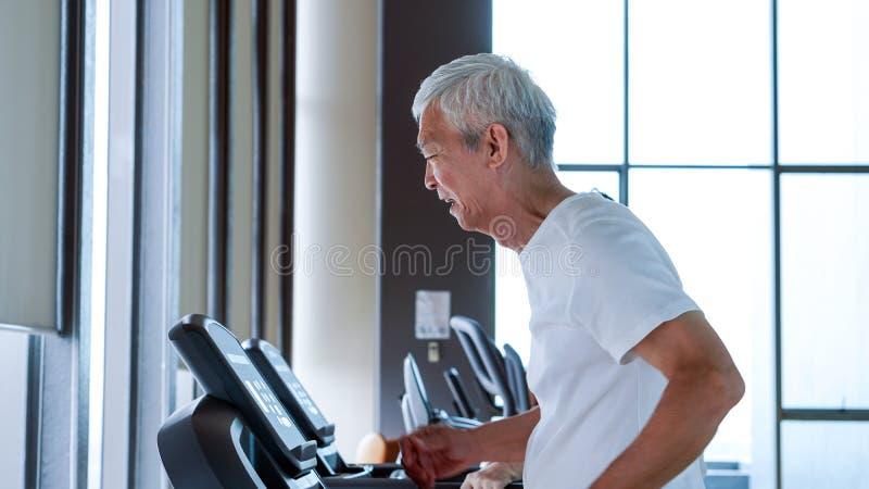 Gesunde asiatische ältere Paare trainieren zusammen in Turnhalle laufendem tre stockbild