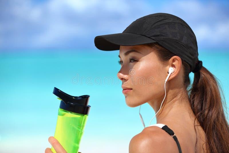 Gesunde asiatische hörende Musik des Trinkwassers des Mädchens lizenzfreies stockbild